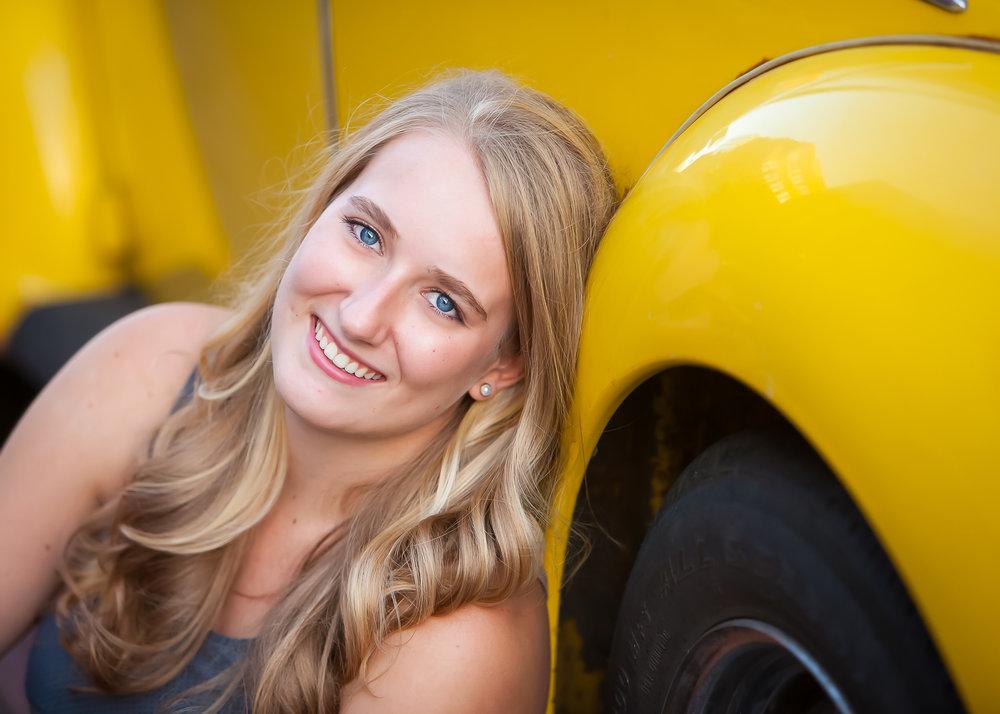 Senior poses with her VW Beetle car in Denver with photographer Jennifer Koskinen, Merritt Portrait Studio