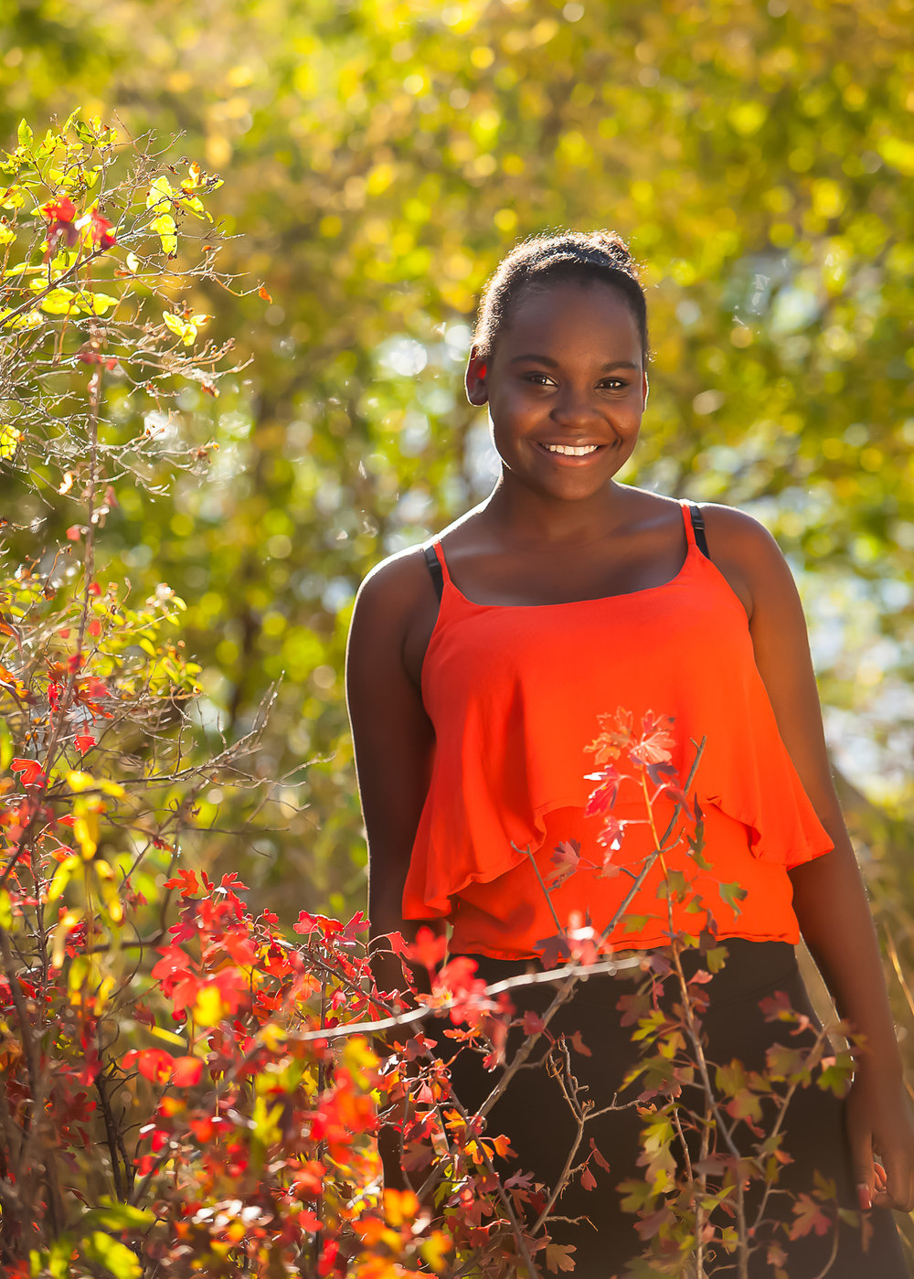 Senior pictures of gorgeous young African American woman in autumn foliage, with Denver photographer Jennifer Koskinen, Merritt Portrait Studio