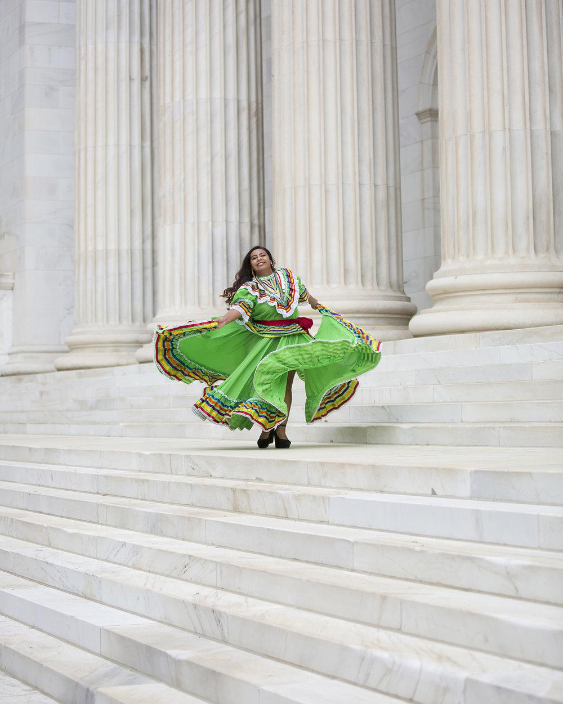 Latina High School Senior Girl Portraits, photographed in Denver with marble columns while dancing in Mariachi dress with photographer Jennifer Koskinen, Merritt Portrait Studio