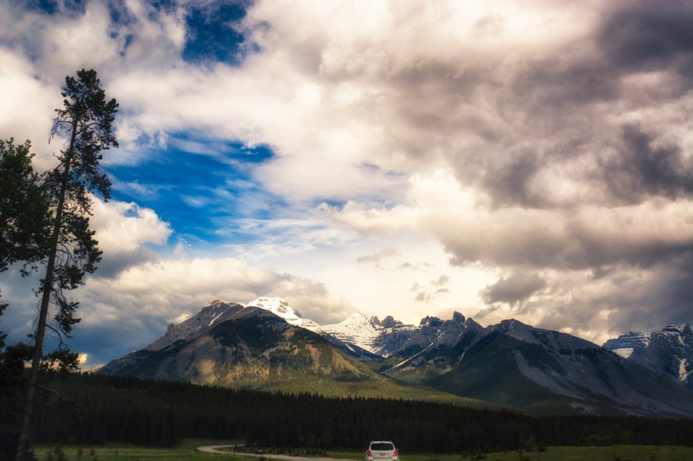The clouds break up and sun streams through, just as we approach the Rocky Mountains, near Banff National Park, Alberta. Hooray!
