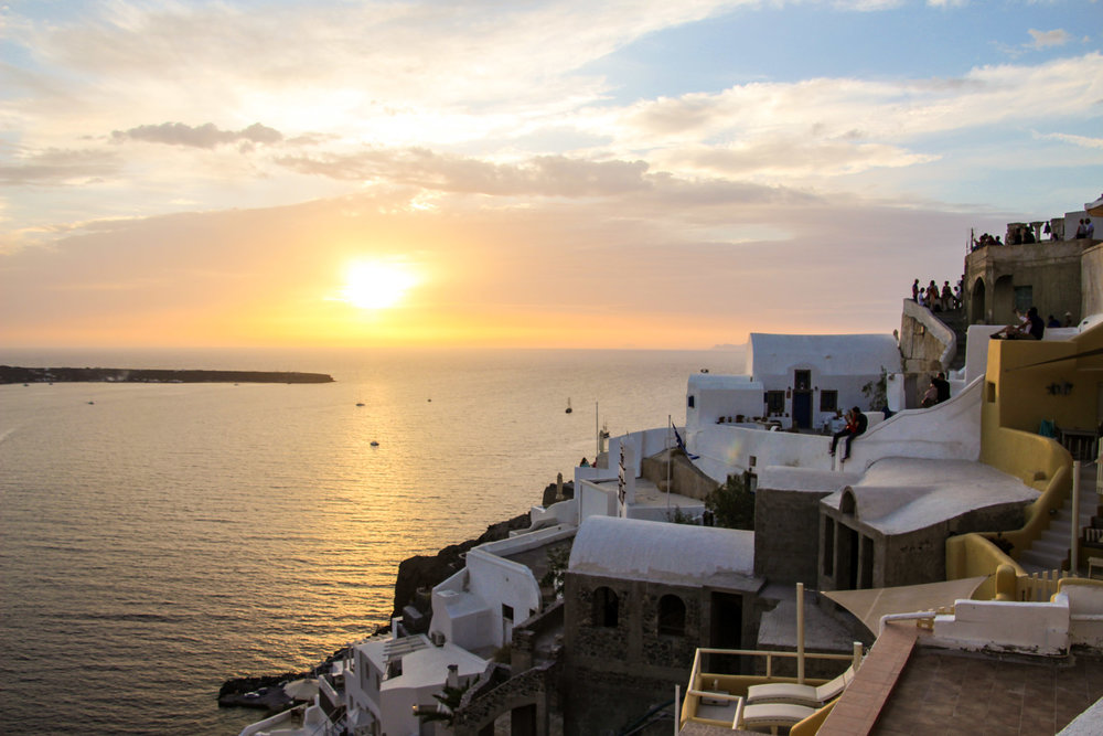 People perched everywhere to catch the sunset. Oia, Santorini, Greece.