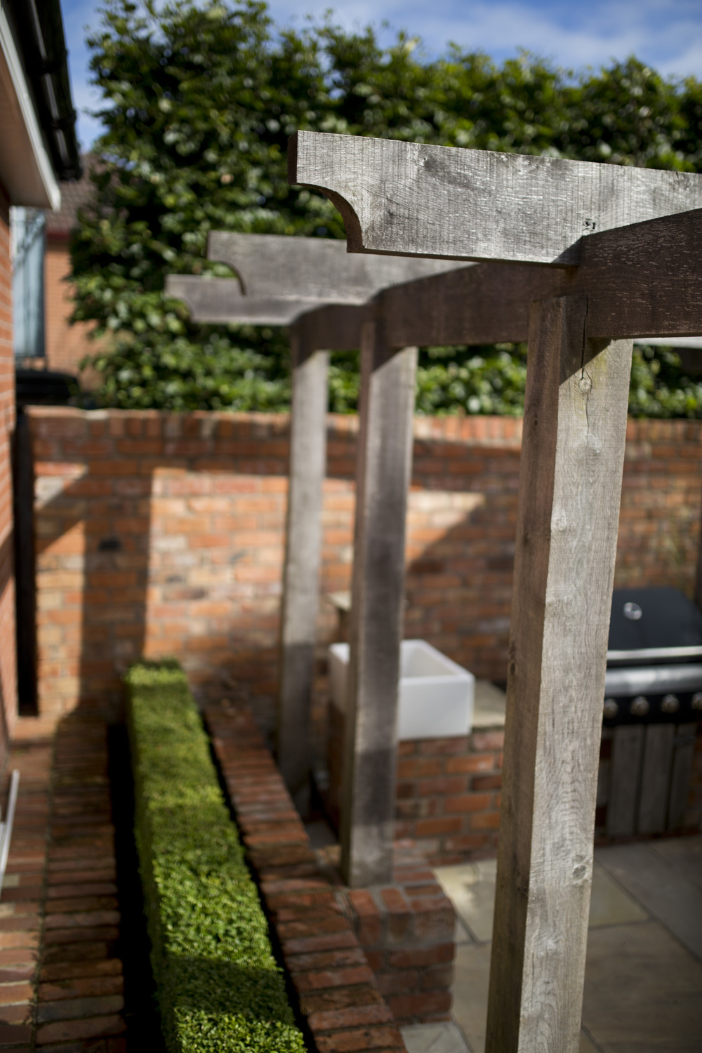 courtyard garden with oak pergola and belfast sink at bbq area