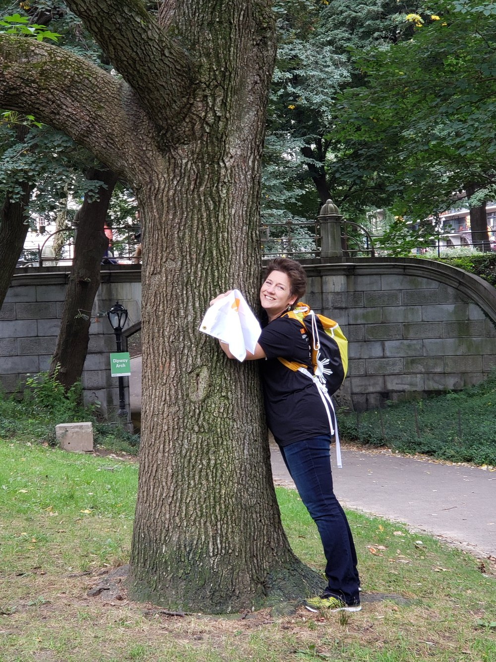 Gina hugs a the New York State tree, the Sugar Maple, to cross off a Questival task