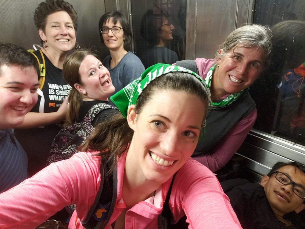 Eight bodies, and two wheelchairs crammed in a subway elevator, Rachel is the only one you can't see.