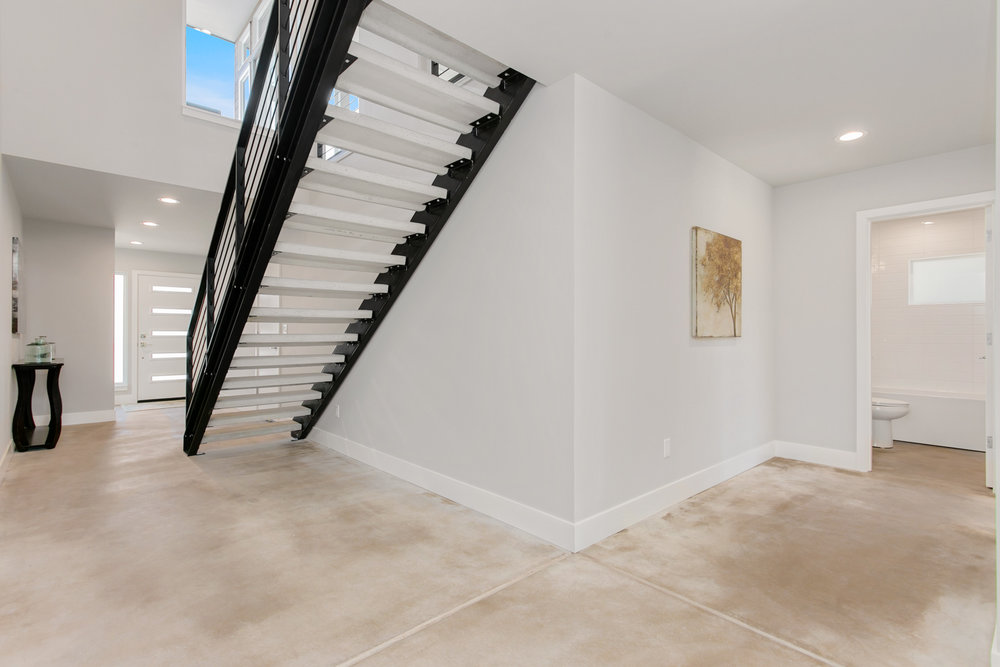 Custom made steel stairway with concrete steps leads you from the entry foyer to the second level.  First floor has sealed concrete floors with embedded radiant heating tubes.