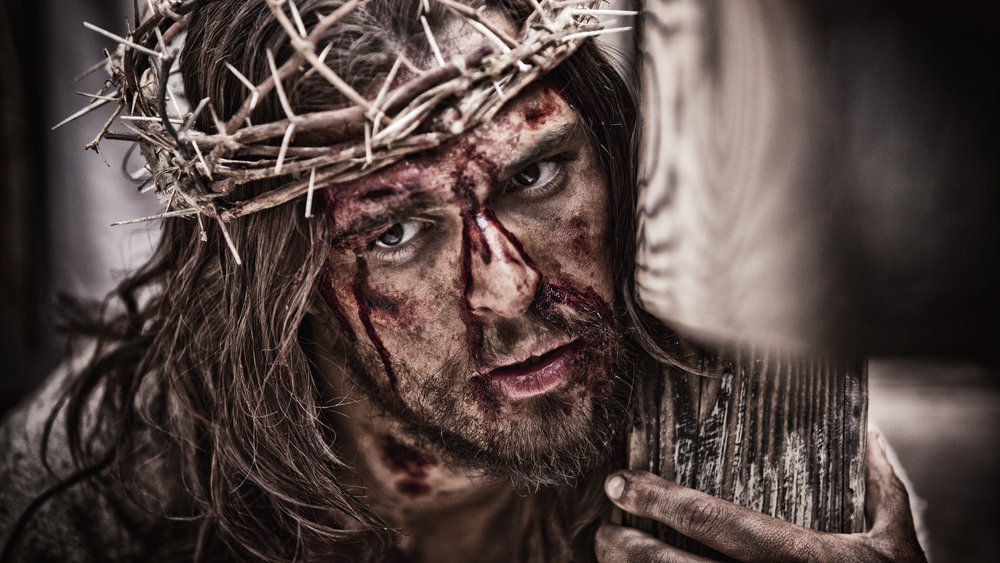 Jesus holding cross with bloodied face.jpg