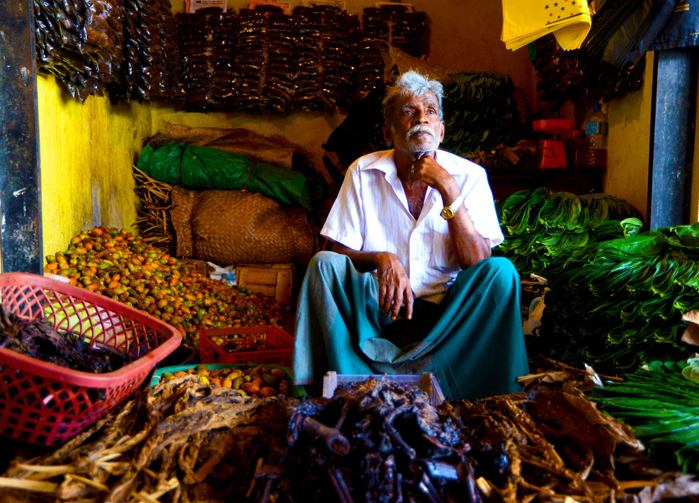 A market vendor sits amongst his goods for sale in Trincomalee, Sri Lanka, on August 10, 2014.