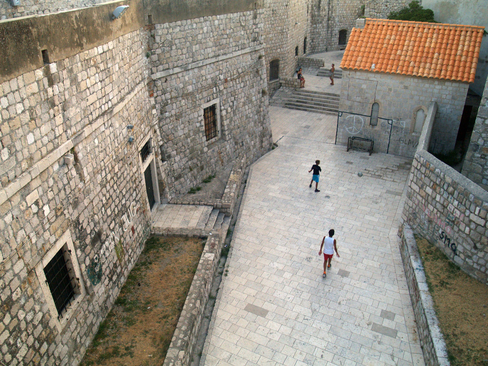 Boys play behind Dubrovnik's old city wall.