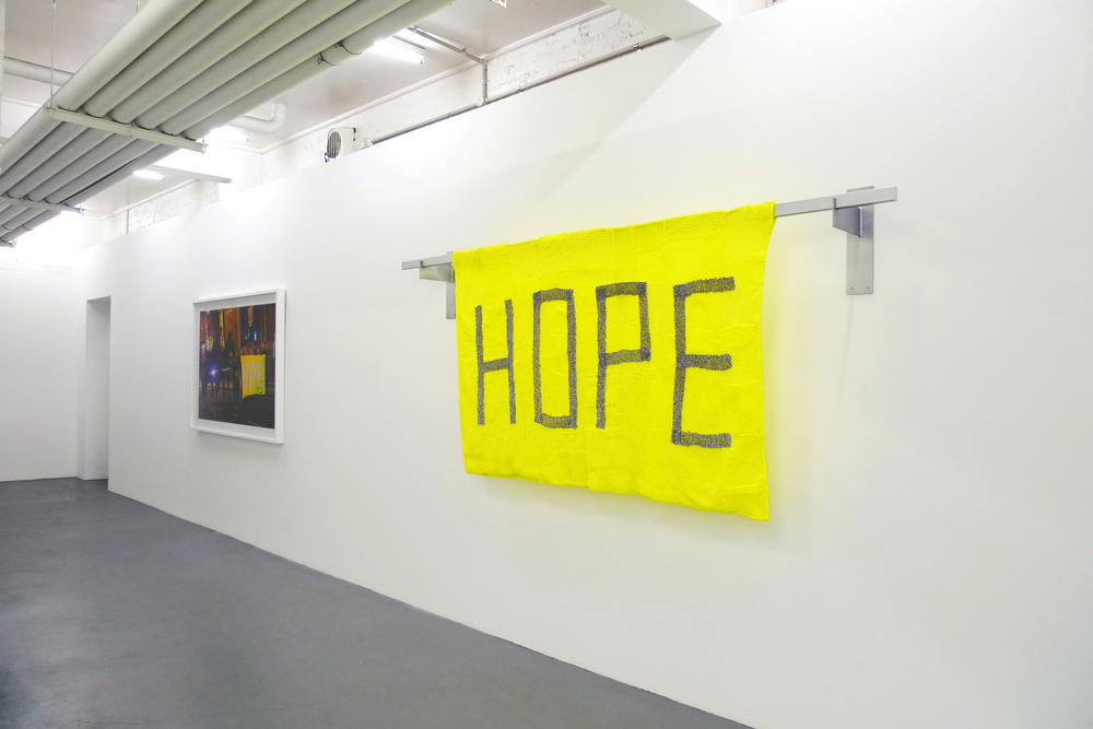 Kate Just, HOPE & SAFE, 2014 Banners: Hand knitted builder's line and retroreflective silver thread, viscose, cotton, aluminium, steel, paint 280cm x 125cm x 25cm Photographs: Digital Type-C print (framed). 120 x 170cm Documentation: Simon Strong and Daine Singer