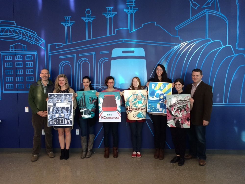 Some members of the KCAI Illustration elective class, MICRO, Fall 2015.  Students are holding up posters they created to announce the new KC Streetcar. Pictured left to right is; David Terrill, Kate Dittman, Alicia Wyatt, Erin Mulhausen, Matti Crabtree, Emily Woodson, Karolina Akimov and Tom Gerend, Executive Director of The Kansas City Streetcar Authority.