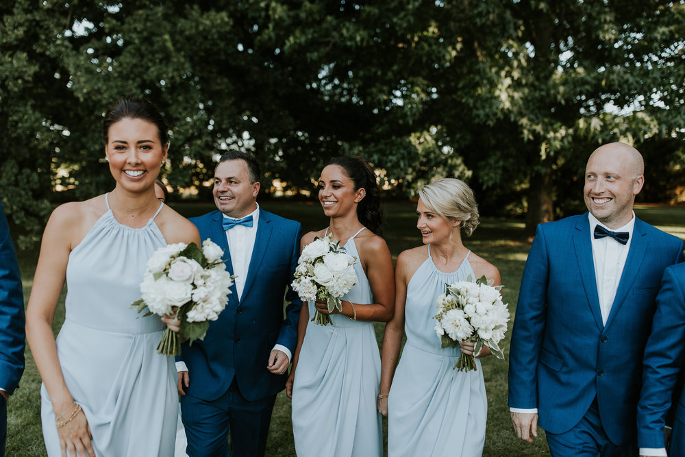 "Keli's bridesmaids wore Shona Joy dresses in powder blue. ""They were simple and elegant and the girls looked beautiful beside the groomsmen in their navy suits."""