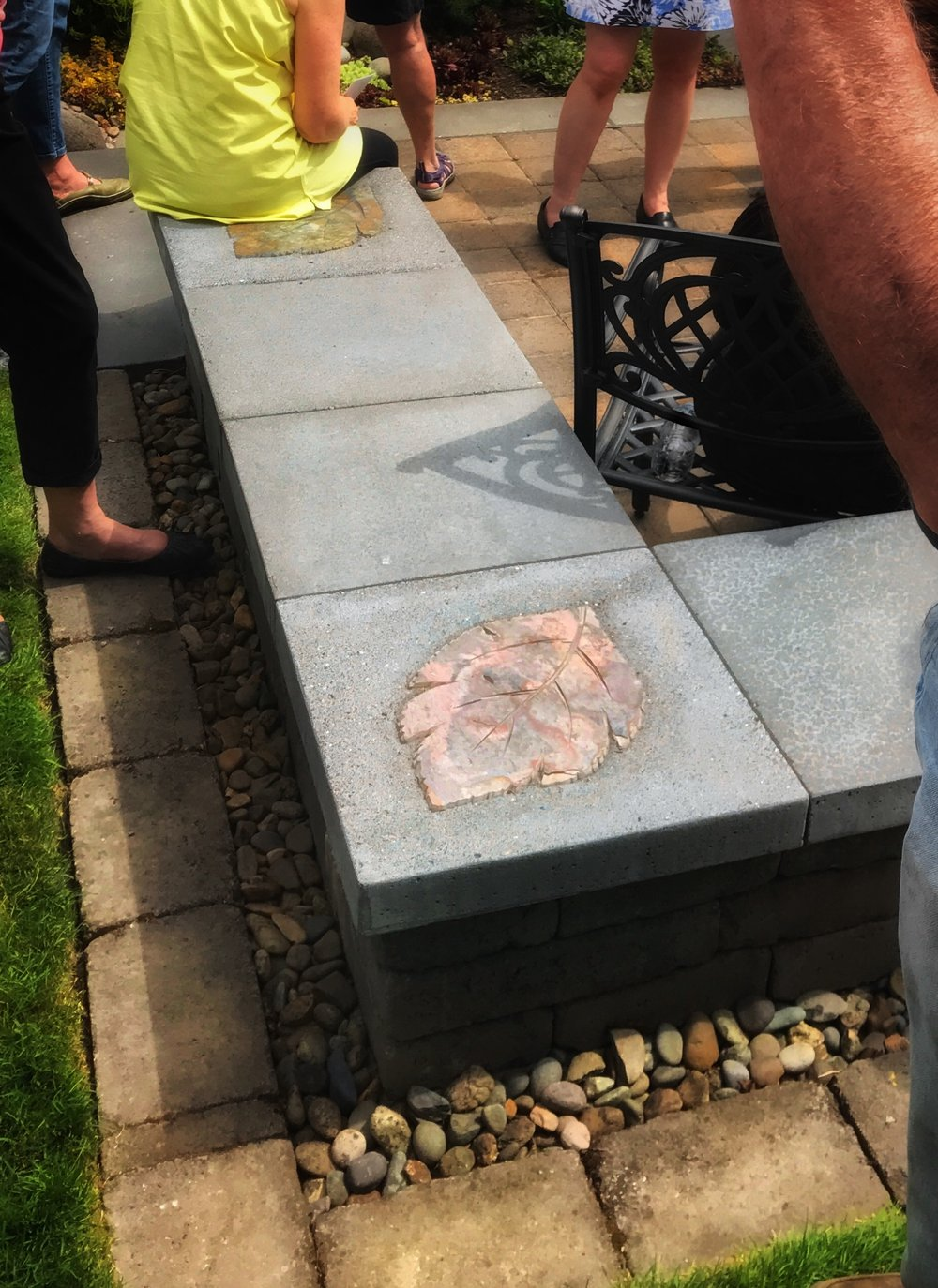 "Marcia Peck handiwork in evidence here, understated and perfect. Marcia's carvings, inlaid in concrete cap stones, installation by JP Stone Contractors.   This garden has great ""seat walls"" surrounding dual patios. Diagonally-placed patios maximize a small space and the slope.Readily-available pavers are used in varying sizes and in interesting patterns."