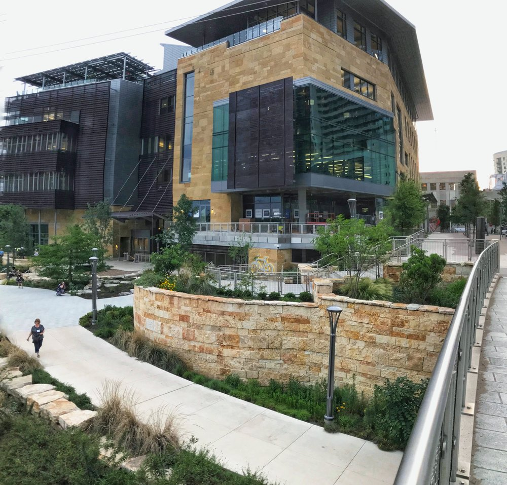 Portland blogger Loree Bohl walks along Shoal Creek Trail, with Austin Central Library behind.