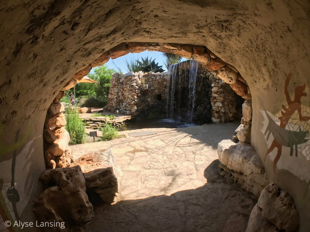 """This was my favorite part of the garden, approaching as I did from the back. From that side, the tunnel's destination and purpose is mysterious. The pictographs inside surprised and delighted me, and beyond—that waterfall! What had been hidden, unfolded in a secret grotto. It was only """"secret"""" for a moment, but I enjoyed that brief fantasy."""