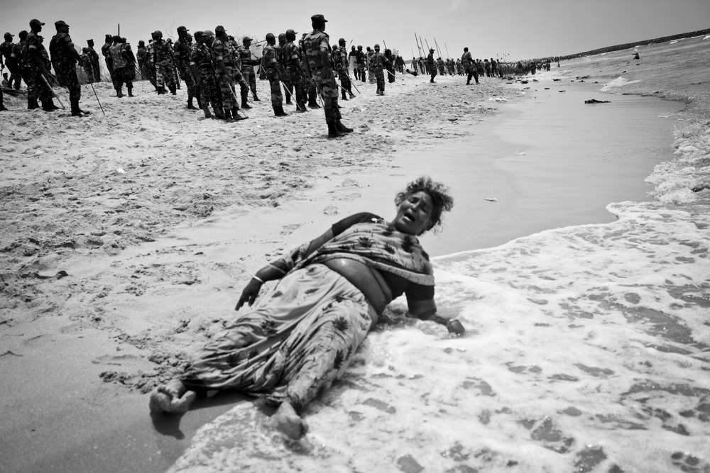 Xavieramma, a resident of Idinthakarai, cries out for help after being chased into the sea with no place to run. She is later both helped and arrested by security forces, and is subsequently charged with 16 offenses including the serious charges of sedition and waging war against the nation.