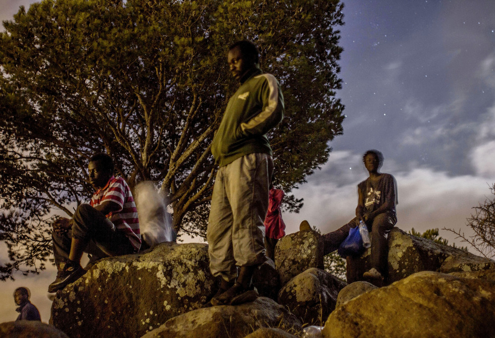 A group of migrants watch the flickering lights of the Spanish port city of Melilla from their perch atop Mount Gurugú, a last resting point before they attempt to scale the city's walls in search of a passage to Europe.
