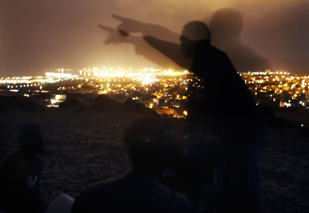 A group of immigrants plan their path over the barricades that separate Africa from the European exclave of Melilla.