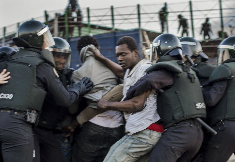 African immigrants hoping to avoid immediate deportation struggle with police after jumping the border fence from Morocco. EU law bars its states from implementing the immediate deportation of immigrants, allowing anyone who steps foot on European Union territory the chance to apply for political asylum.