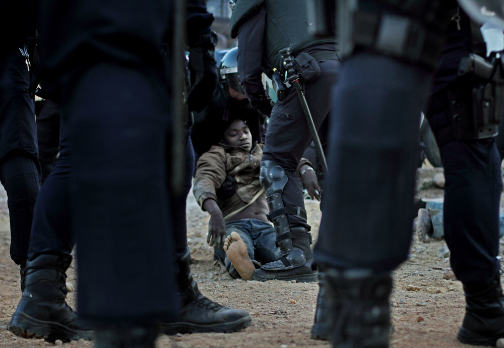 An injured immigrant beaten unconscious in a struggle with the Spanish police in Melilla.