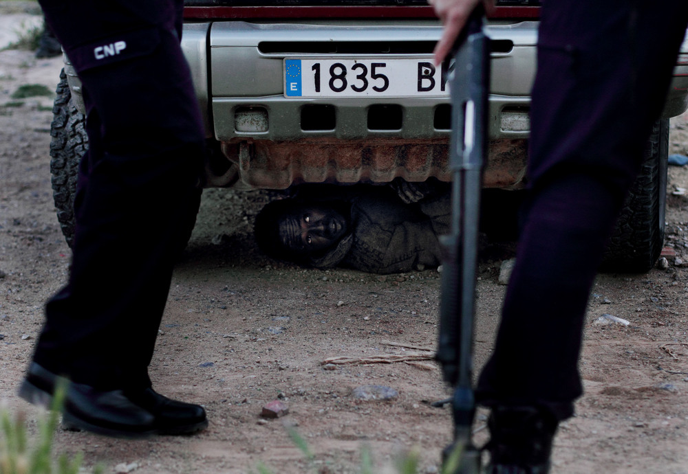 Attempting to avoid deportation back to Morocco, a recent immigrant hides from Spanish police under a vehicle. European Union law bars summary deportations and requires members to allow anyone who steps foot on their territory to apply for political asylum.