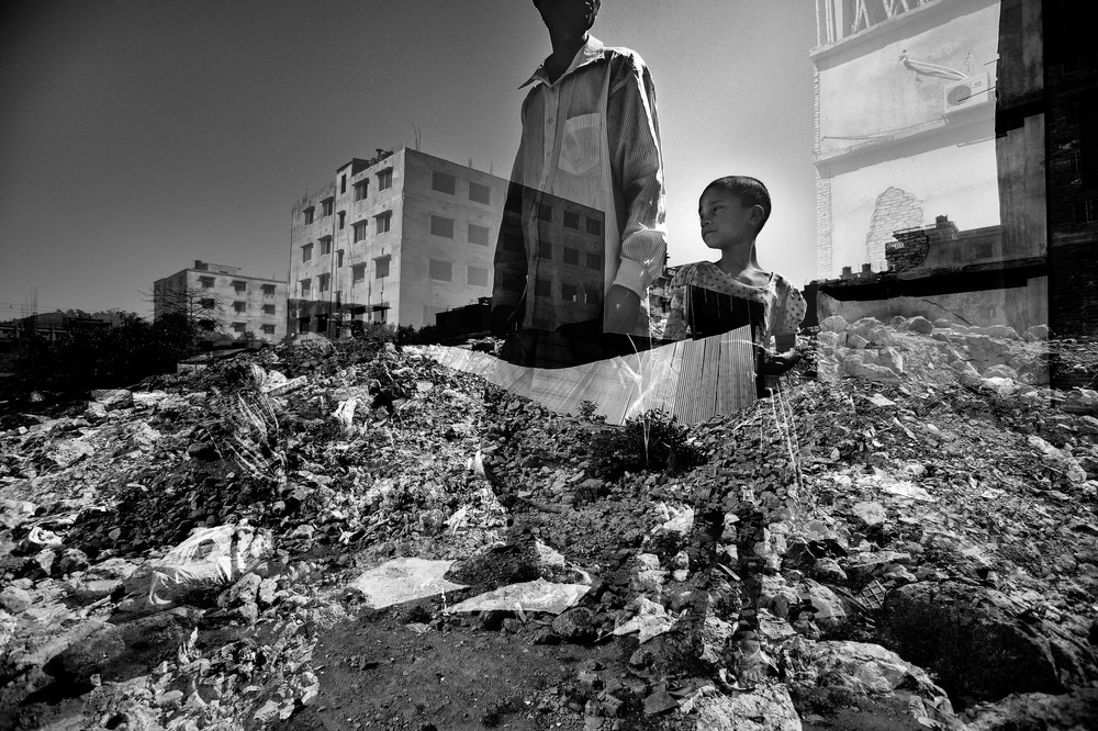 A man with his daughters wandering through the ruins of Rana Plaza.