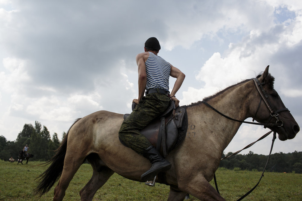 "Students train horse-back riding at the Historical War Camp, in Borodino, Russia. July 28, 2016. The project statement of the camp says: ""To awaken in the younger generation a keen interest in the history of the Fatherland, the glorious deeds of our ancestors, to facilitate the expansion of military-historical knowledge."" © Sarah Blesener"