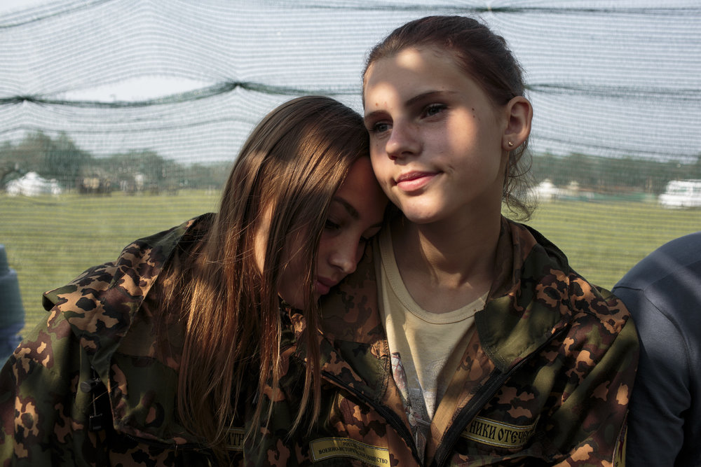 "Nastya Gobritskaya (L, 15) from Moscow and Alina Klikova (R, 16) from Medin at the Historical-War Camp, in Borodino, Russia. July 26, 2016. The project statement of the camp says:  ""To awaken in the younger generation a keen interest in the history of the Fatherland, the glorious deeds of our ancestors, to facilitate the expansion of military-historical knowledge."" © Sarah Blesener"