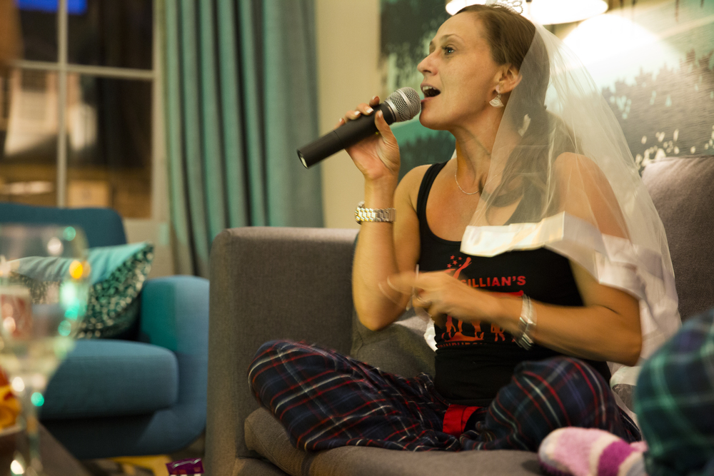 Gillian sits on the couch and sings karaoke, still wearing her veil with her pajamas.