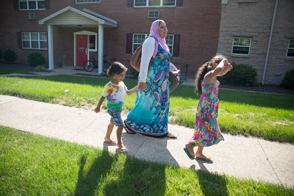 Mona Soweilam walks with her children Gamal El Sayed, left, and Ruwan El Sayed, right, outside of their apartment in Camp Hill. Mona and her family recently moved out of her sister's house, where many of their extended family members live.