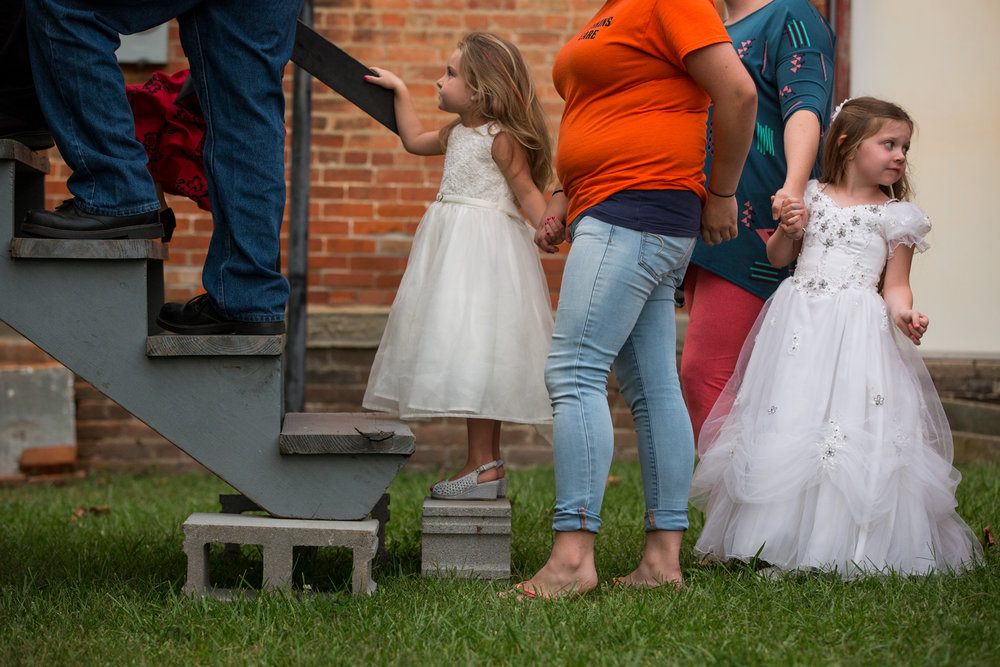 Bayleigh Merrill, 4, left, and Morgan McKinniss, 4, right, hold hands with their mothers, Leah Smith, center left, and Misty McKinniss, center right, as they wait to walk onto the stage to be introduced during the Mini Queen Contest on the first night of the Wellston Coal Festival on September 5, 2017, in Wellston, Ohio. The festival has been held every year since 1973.