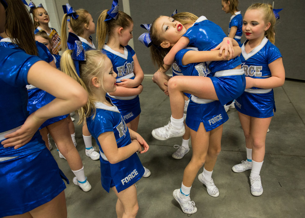 A cheerleader carries her friend as they wait in a room adjacent to the stage before being called to perform their routine during the Arnold Cheerleading and Dance Team National Championships in Columbus, Ohio, on March 4, 2017.