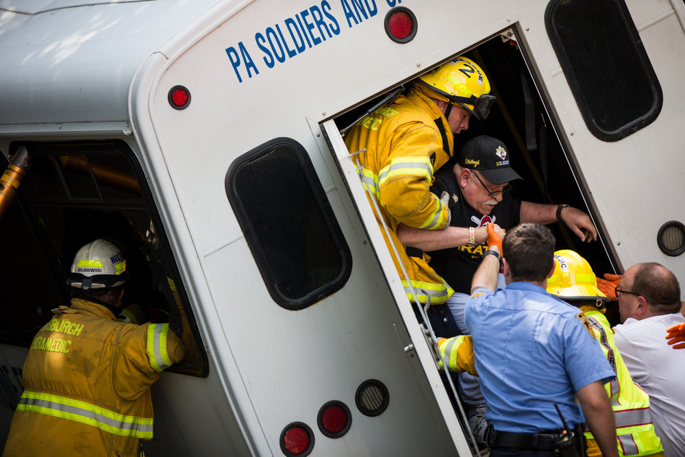 Paramedics help wheelchair-bound Joe Allessie out of a bus that crashed into a nine-foot overpass on Thursday, July 20, 2017, in Pittsburgh's North Shore. The group of veterans came down to Pittsburgh from the Pennsylvania Soldiers' and Sailors' Home in Erie to attend a tailgate party and watch a Pirates game. No one was seriously injured in the crash, and the passengers were still able to make the game.