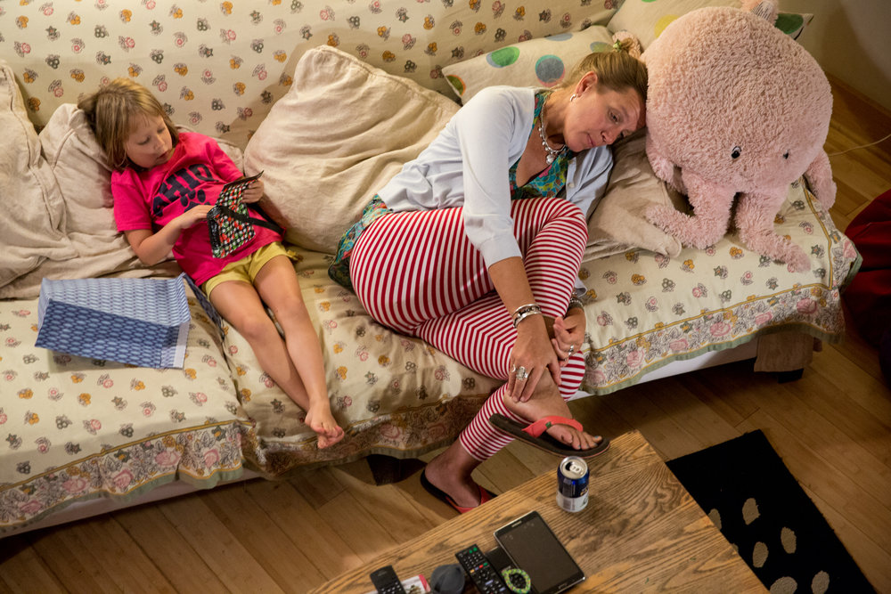 Wendy Minor Viny lays on the couch next to her daughter Nina Viny, 5, at the end of the day at her home in Meigs County, Ohio, on September 4, 2015. Viny spends her mornings working with adults with disabilities at Passion Works Studio where she is a resident artist and her afternoons caring for her children when they get home from school.