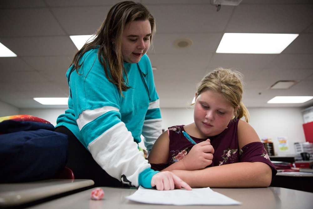 Raegan, a junior at South Webster, helps her buddy, Taylor, with her math homework. Raegan wants to help her buddy to develop a positive outlook on life, even if her situation at home is difficult.