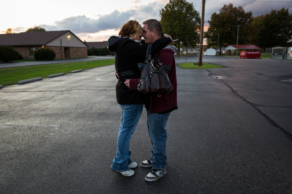 """Whitney Johnson and Jeremy Rhoades hold each other in the parking lot outside of First Baptist Church in Logan, Ohio, before Celebrate Recovery, a Christ-based support group for recovering addicts. Whitney and Jeremy are well known in Logan, Ohio, where Whitney says they were """"the worst of the worst"""" when it came to the addicts in town, but right now they're both clean and trying to stay that way."""