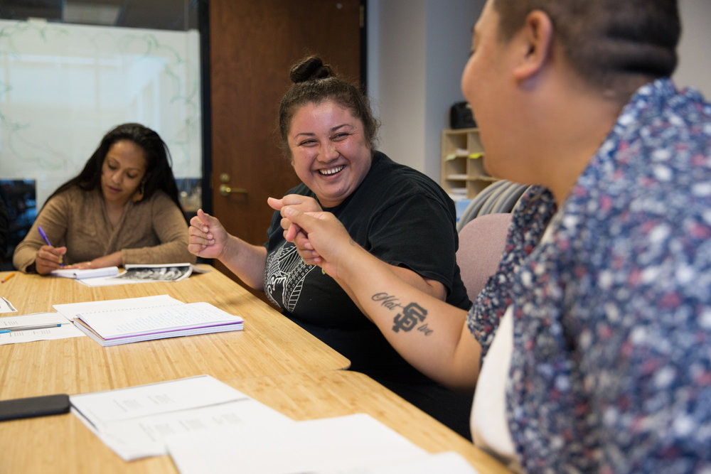 "Lucero Herrera, left, and K.I. Ifopo fist bump after Lucero read her poem out loud during a Writing to Power workshop. Many of the staff members knew each other before coming to the center, like Lucero and K.I. who were incarcerated together, and have continued to build a bond through their work. ""It's like special magic goes on in this place because of the people that are here. We create our own kind of love and our own kind of care for each other,"" K.I. said."
