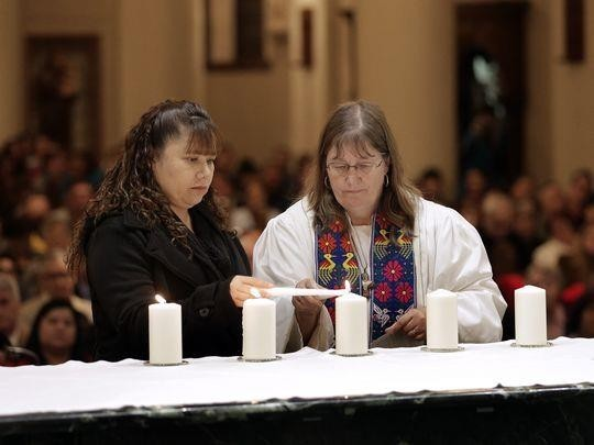 Rev. Deborah Clugy-Soto  lights a candle with refugee Maria Alvarado of Mexicanos Auxilary after their testimony Thursday at St. Patrick Cathedral. The Hope Border Institute hosted an interfaith community  gathering Thursday to join in solidarity with the immigrants of the El Paso area. (Photo: MARK LAMBIE /EL PASO TIMES)