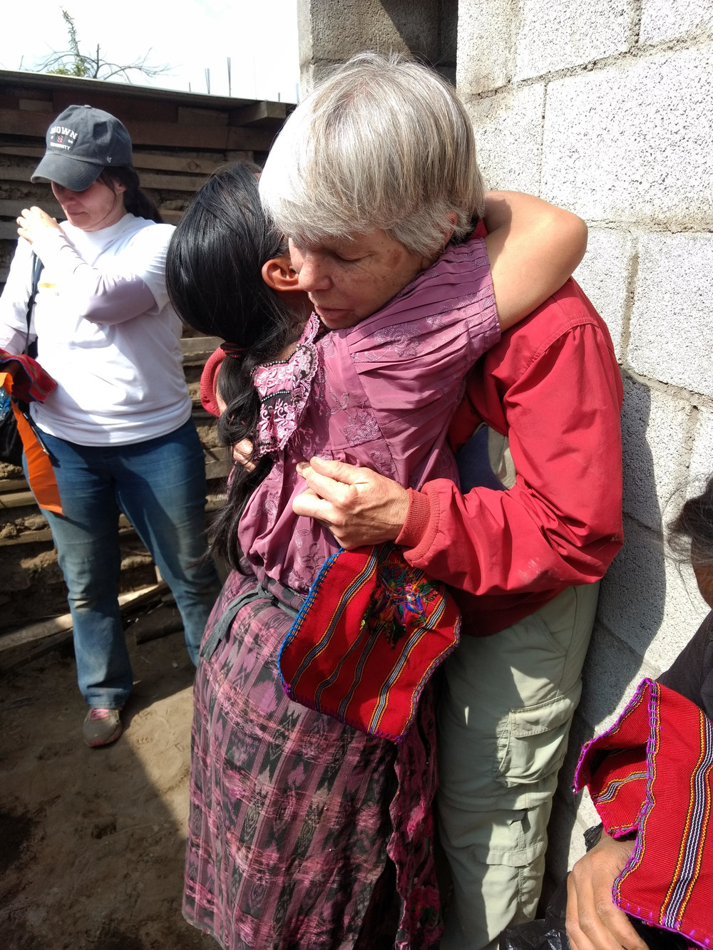 The family at the second house made a weaving of the volunteers. This photo shows Pamela receiving her weaving from Blanca.