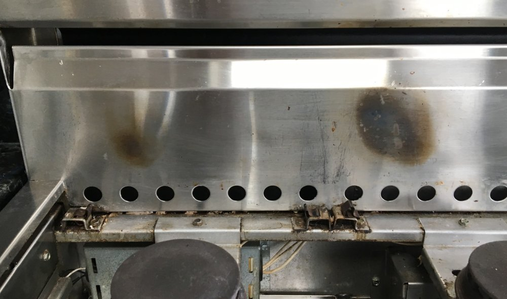 Stainless Steel Range Burn Marks Before Restoration