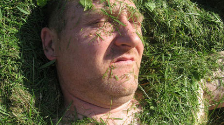 Local Brisbane man covered in lawn clippings from lawn mowing.
