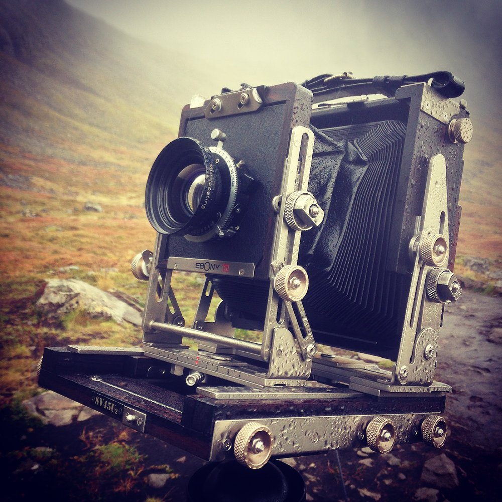 A large format camera up a hill, waiting for the rain to stop. Peak analogue.
