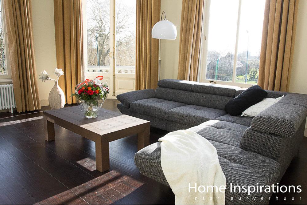 Woonkamer luxe grijze bank met okergele gordijnen