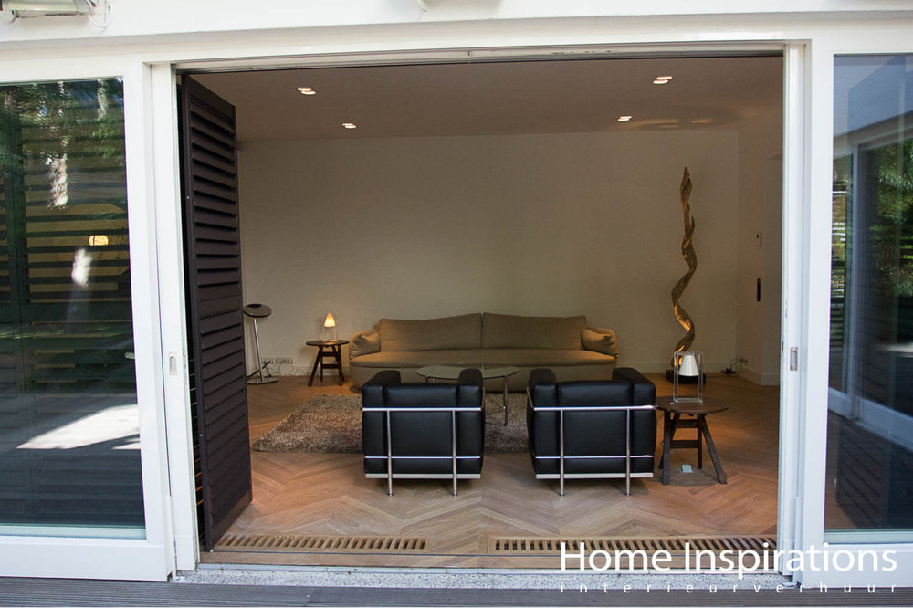 Woonkamer openslaande tuindeuren met design fauteuils