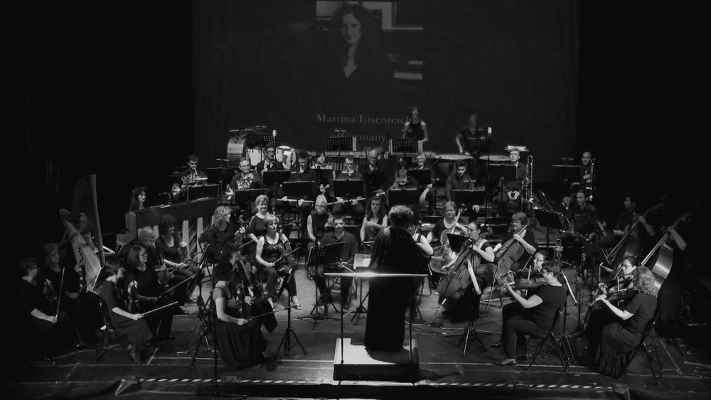 Martina Eisenreich conducting the Rousse Philharmonic Orchestra (1, B&W), 2017. Foto by LAFCI / Christoph Müller-Bombart. [592 KB]