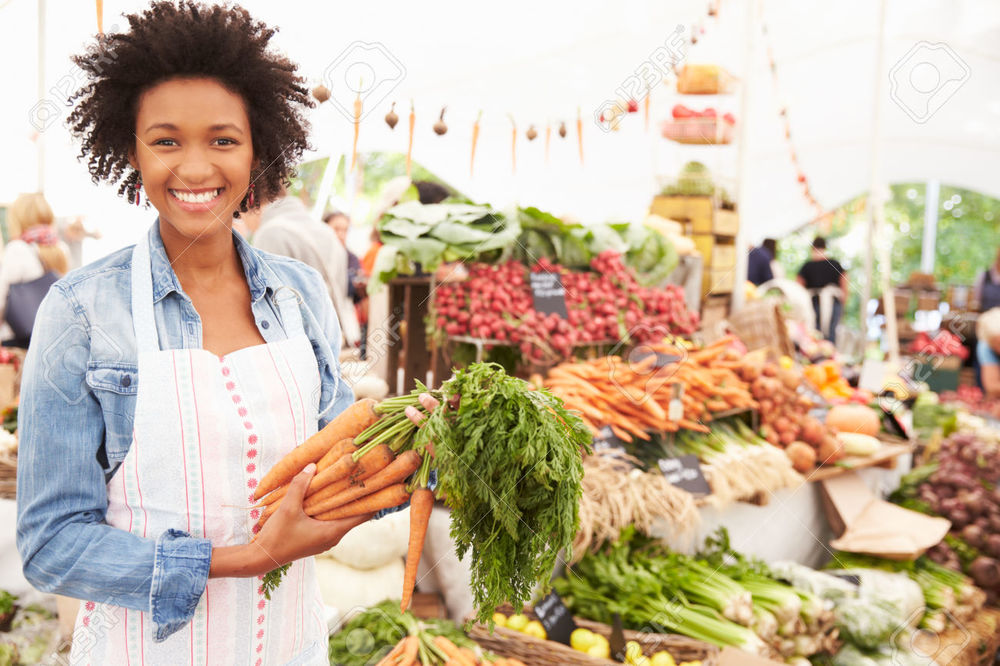 42131604-Female-Stall-Holder-At-Farmers-Fresh-Food-Market-Stock-Photo.jpg