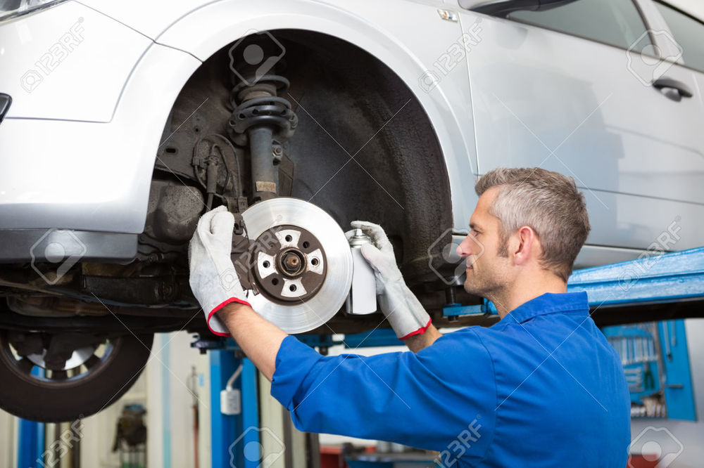 50287034-Focused-mechanic-adjusting-the-wheel-at-the-repair-garage-Stock-Photo.jpg