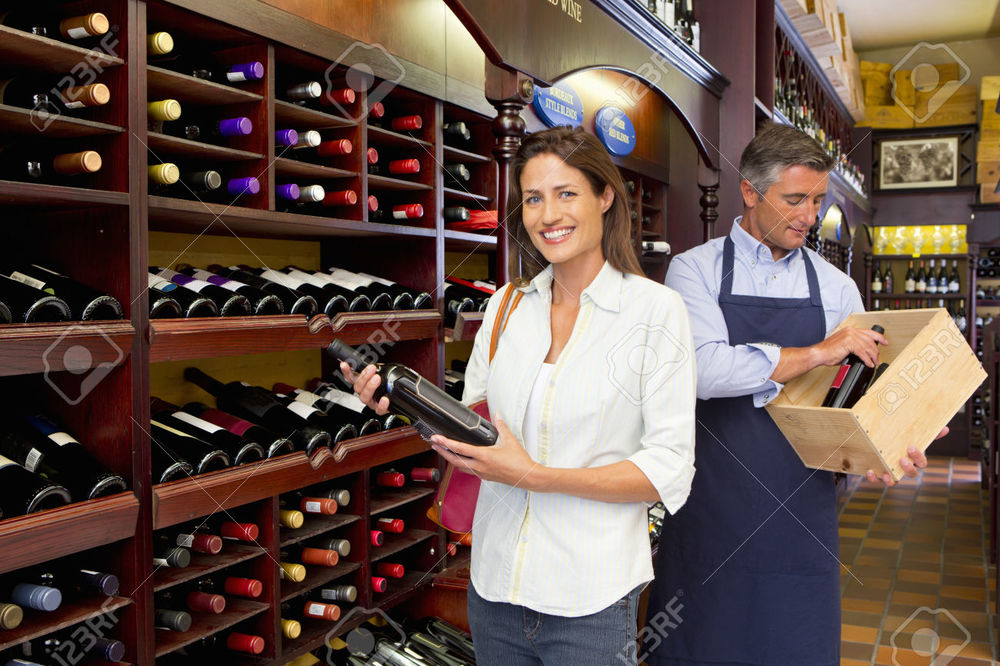 37954967-Smiling-customer-and-worker-holding-bottles-in-wine-shop-Stock-Photo.jpg
