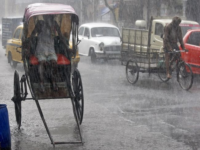 A man takes shelter inside his rickshaw during a heavy rain shower in Kolkata on June 25, 2015. (Reuters photo)