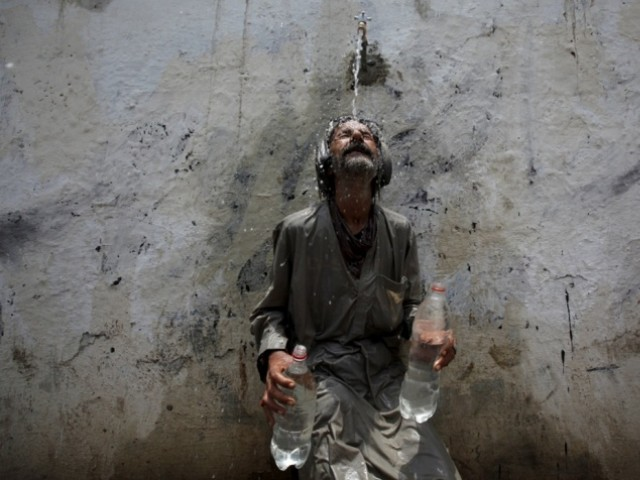 A man cools off under a public tap in Karachi. PHOTO: REUTERS