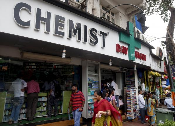 People walk past a chemist shop at a market in Mumbai, June 25, 2015. REUTERS/SHAILESH ANDRADE